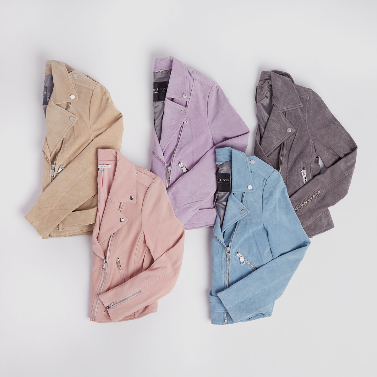 Five women's suede jackets in varying colors laid flat on a grey background.