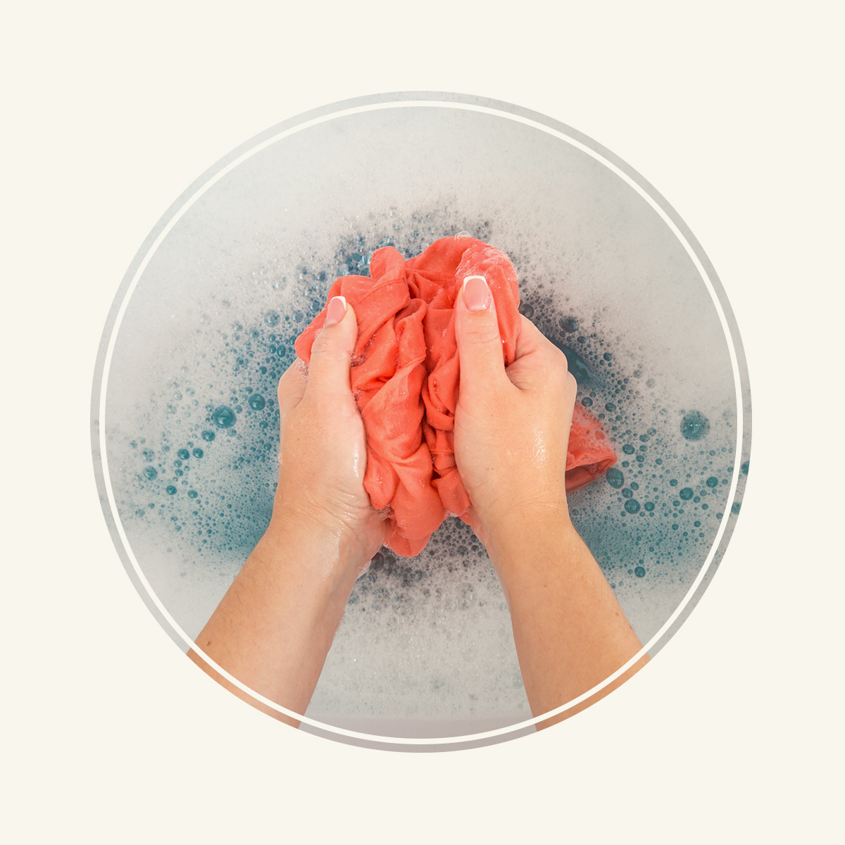 Close up of a woman's hand washing a pink cashmere sweater in soapy water.