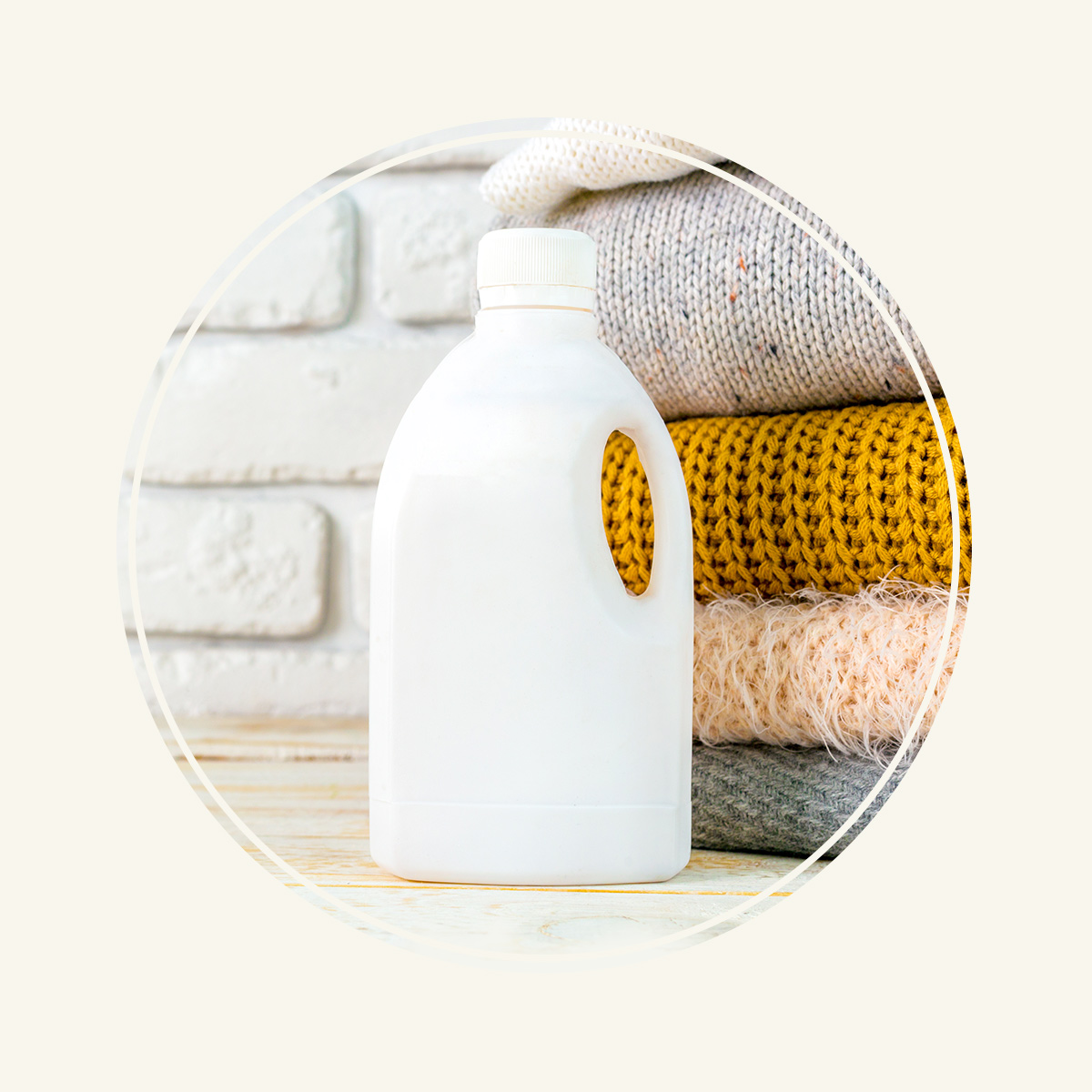 Stack of folded sweaters and white detergent product on wooden counter attached to a white brick wall.