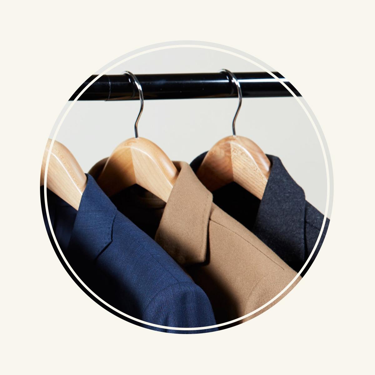 Three men's wool blazers on wooden hangers.