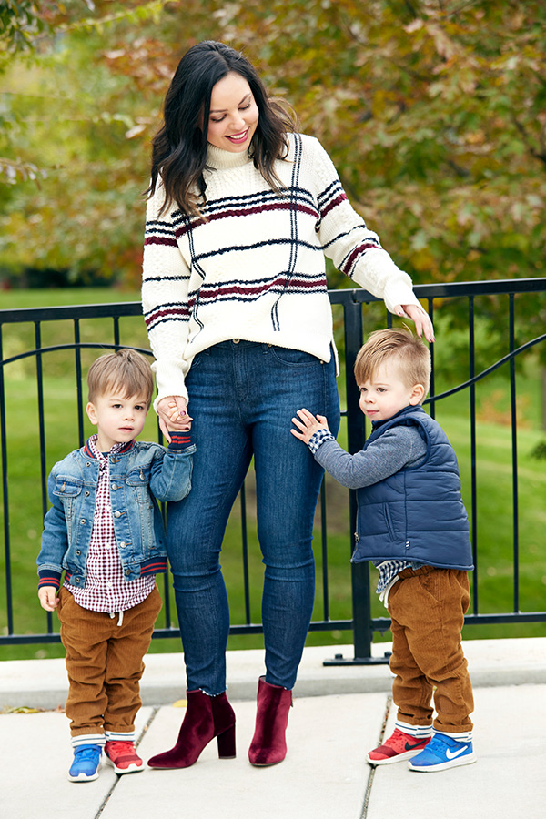 A mom and her two young boys standing in a park during the autumn.