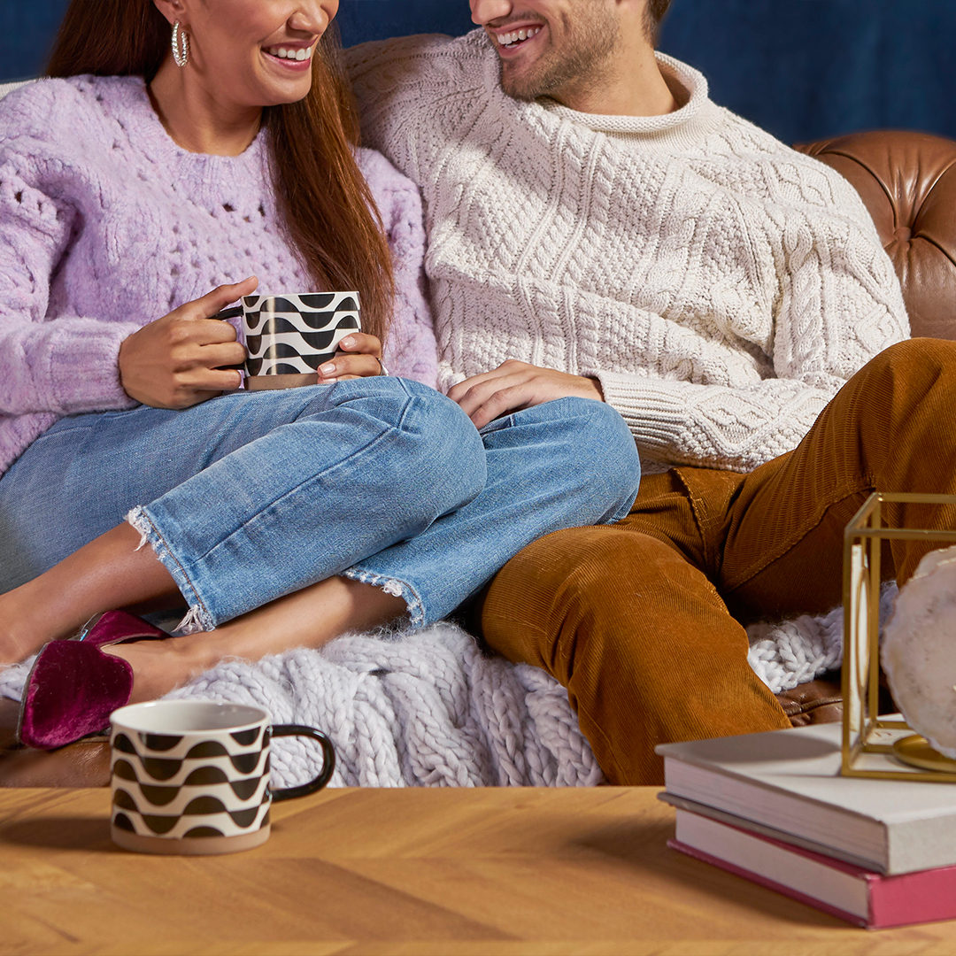 Couple sitting on couch wearing sweaters.