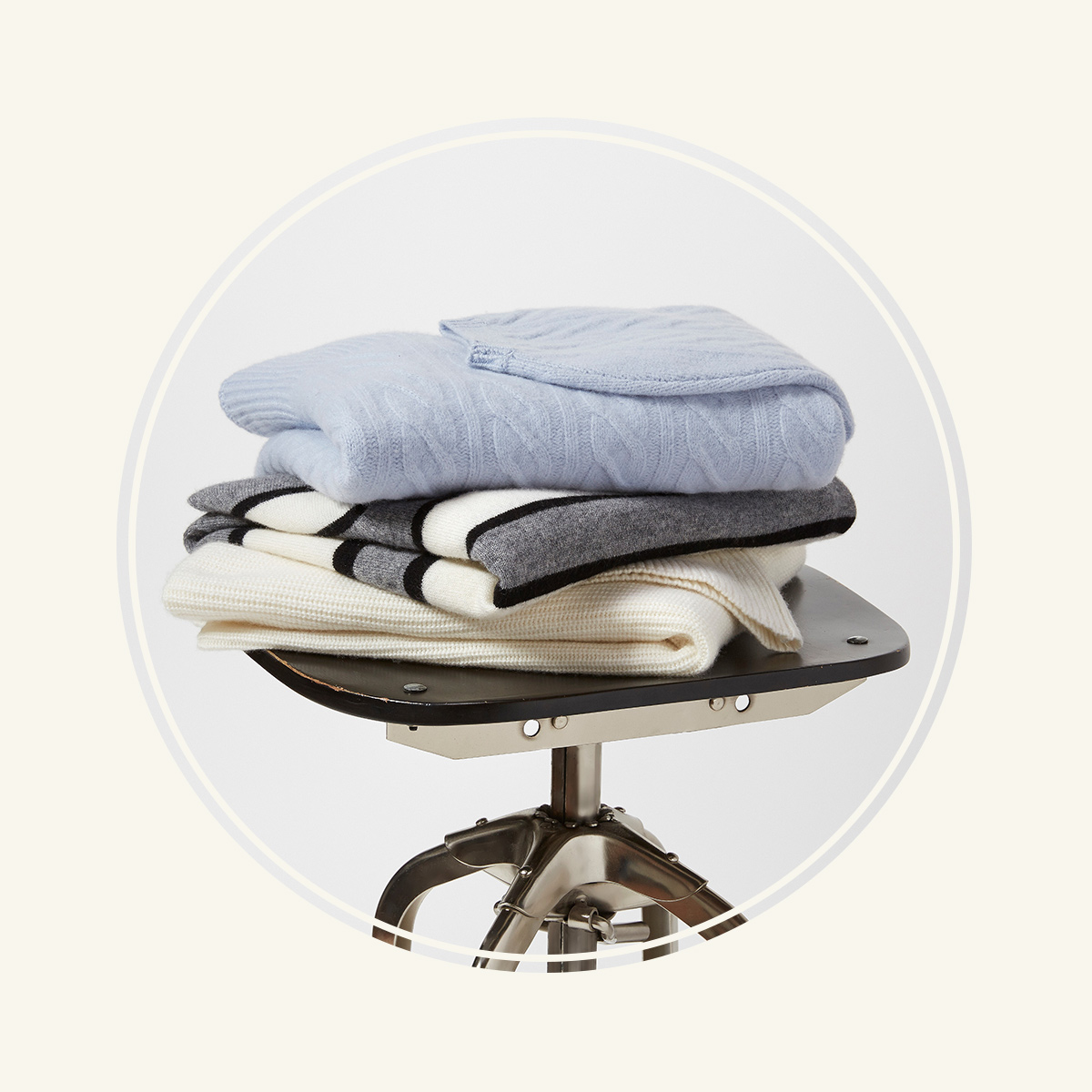 Stack of sweaters on a stool.