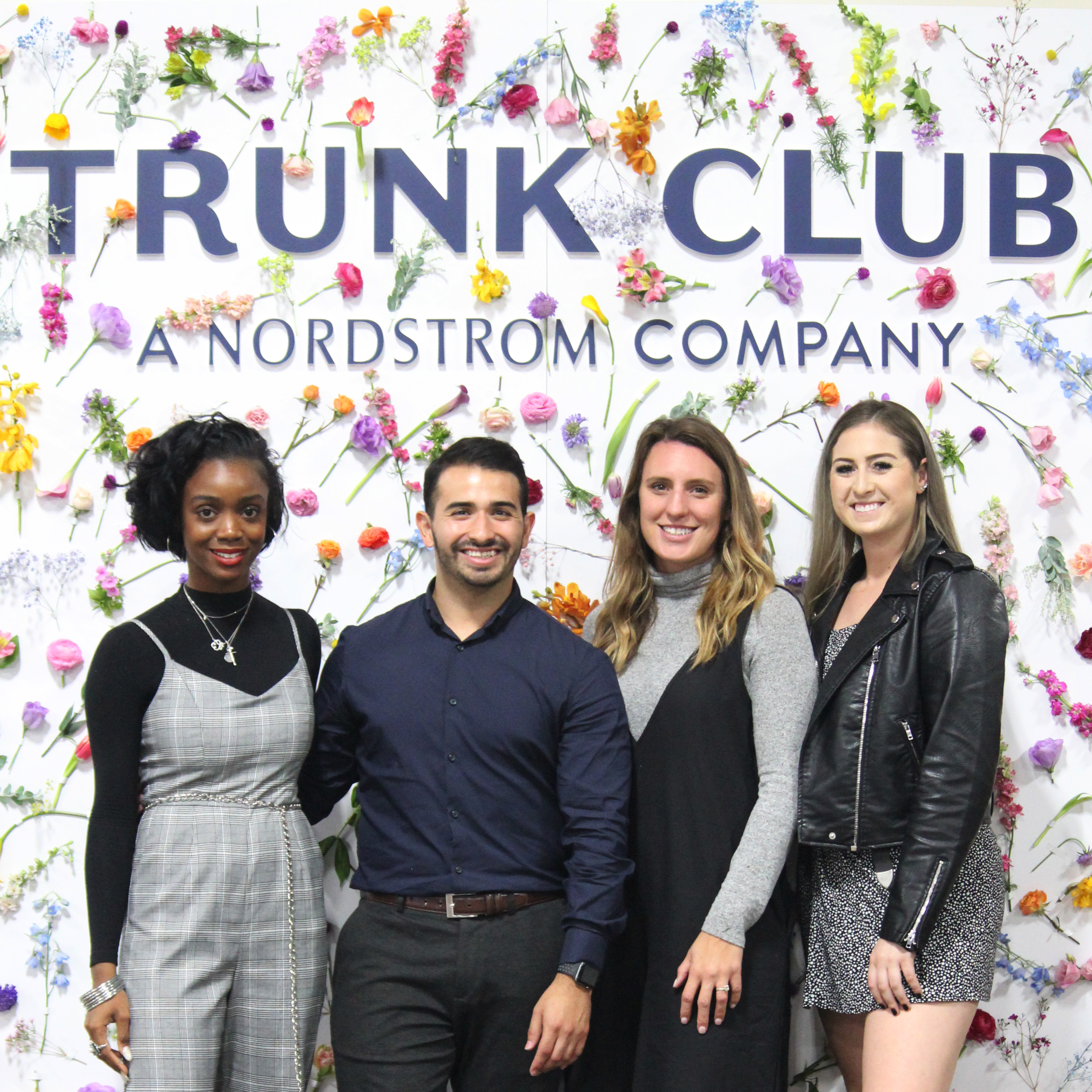 Group of four in front of a Trunk Club Instagram wall covered in flowers.