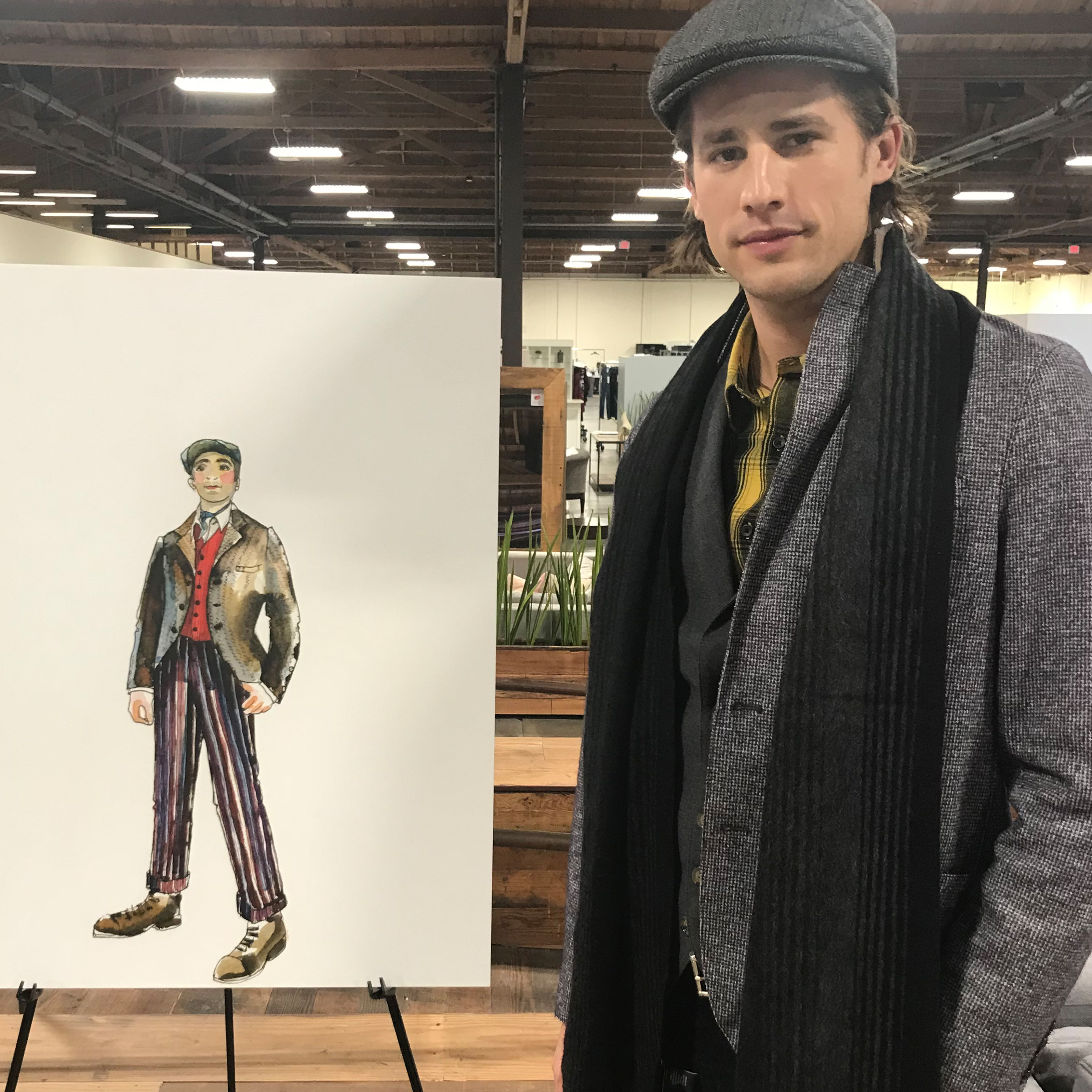 Model standing by sketch of his outfit.