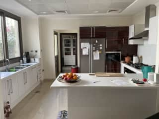 Fully equipped kitchen with gas stove and oven, microwave, fridge. Behind the kitchen is the laundry area with washer-dryer and a separate pantry.