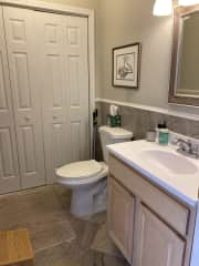 Half bath next to kitchen. Laundry and cleaning supplies behind folding doors.