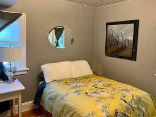 The guest bedroom on the main floor is a full-size bed. It is a across from a full bathroom.