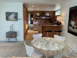 Dining and bar area with kitchen. Hallway with washer / dryer to left, bathroom to right and bedroom beyond.