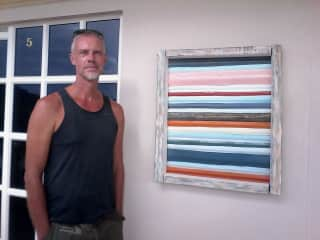 Ebbo next to one of his recycled corrugated metal paintings.