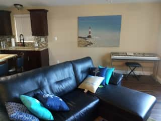 The leather couch, keyboard piano, are in a family room with the front bay windows.