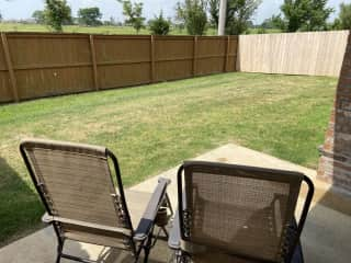 Enclosed backyard with lounge chairs