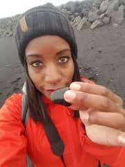 Me in Reynsifjara, Iceland at the black sandy beach holding a black rock. Don't worry, I put it back.