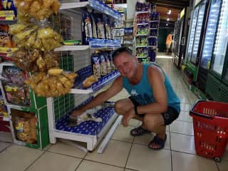 Food shopping while traveling in Cost a Rica 2018.  Gaetan cannot resist petting the cat owner!