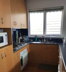 Galley kitchen with gas cooktop, oven, microwave