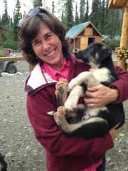 Kathy with puppy from Alaskan sled dog kennel where daughter and son-in-law worked.