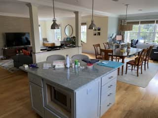 Spacious, sun-drenched living area with large kitchen island, dining room, living room, and office and sitting area