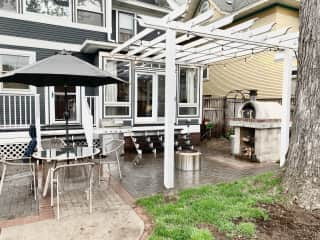 Back patio with woodfire oven, fire pit, and table