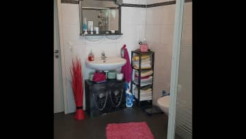 Bathroom with door to storage room with washing machine