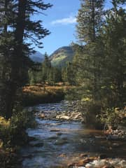 Creek alongside house with view of Continental Divide peaks