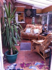 Conservatory with exercise bike, darts board and water fountain