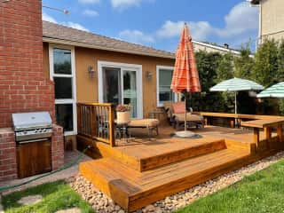 Outdoor deck with cushy furniture and an umbrella.  Adjacent, the two lower umbrellas provide shade for  bunnies' outdoor playpen.