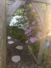 Garden arch with seating nook in summer.