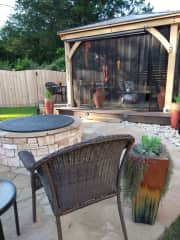 The privacy fenced backyard features a firepit and a mosquito-netted gazebo.