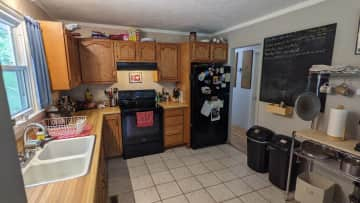 Kitchen view. All major appliances are provided, including microwave, electric stove/over, refrigerator, coffee maker, dishwasher, and garbage disposal.