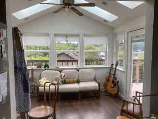 Sun room with an easel for painting and guitars for your use.