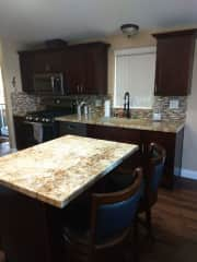 There is an island in the kitchen. The kitchen has a microwave, dishwasher, garbage disposal, and a refrigerator with an ice cube/water dispenser on the door. There are two bar stools at the island, and the corner closet is a food pantry.
