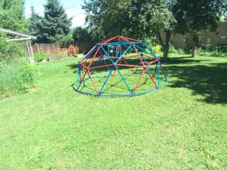 Back yard with play structures, rope swings and raised beds