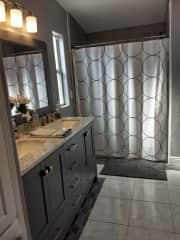 The master bathroom with two sinks and a walk in shower.