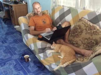 Tiger the cat of Thailand helps Peter with some work.