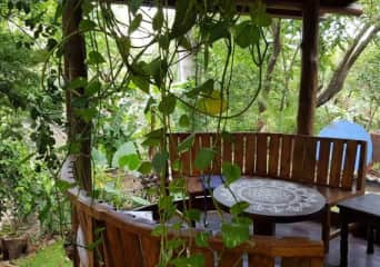 The balcony overlooks gardens and trees along the river.
