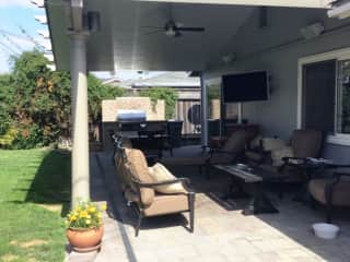 Our backyard patio area w/barbecue, table for 6 for entertaining, tv & outdoor furniture to relax in.
