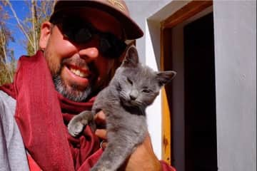 Gregory taking care of a friend's cat in the Himalayas, India 2016
