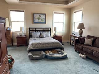 """The east facing master bedroom has a queen sized bed, 2 dog beds, a sofa, and an armoire with TV.  The connecting bath has granite countertops, 2 sinks, a soaking tub with plants all around it, and large shower.  The """"loo"""" is behind a door in the bathroom"""