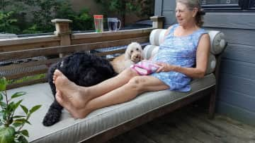 Canada: JoAnn sitting outside with Poppy and Ginger.