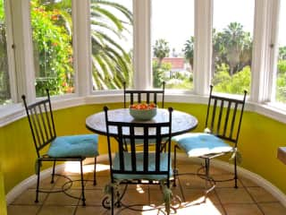 Kitchenette has lovely light and charming breakfast table. NOTE: turret windows have been quite overgrown by palms since this photo.