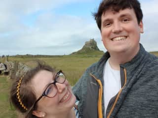 Tom and I on our recent trip to Holy Island, with Lindisfarne Castle in the distance.