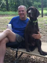 Our dog Garin on a camping expedition, sitting with Mark on his fireside cot