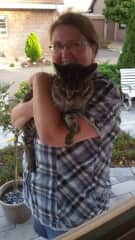 """Cuddling with my cat called """"Winnie"""". She is 15 years old and came to me accidentially. The picture is taken in front of our house."""