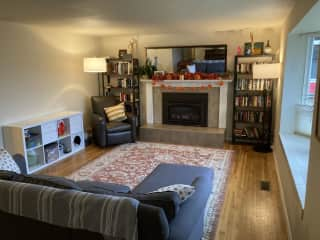 Large living room with bay window, gas fireplace, and lots of books to choose from!