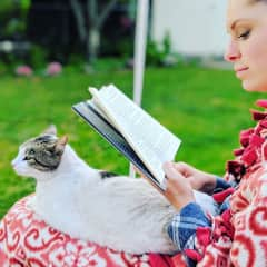 Michaela reading with our cat, Oscar