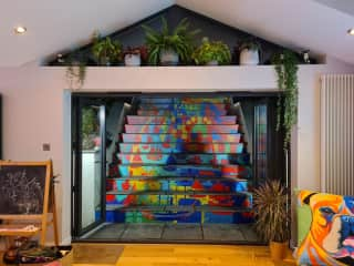 Colourful steps to garden out the back directly off kitchen with large bifolds. Local artist painted the image on the steps!