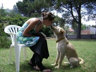 """Here I am with """"Juana"""", the lovely female dog of my sister. She is giving me a kiss and pampering me while I read a book in the park."""
