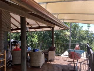 large, undercover deck with fans and tv