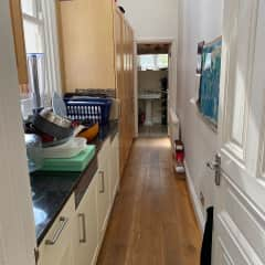 Washer, drier and extra fridge freezer corridor with downstairs toilet and washbasin at the end.