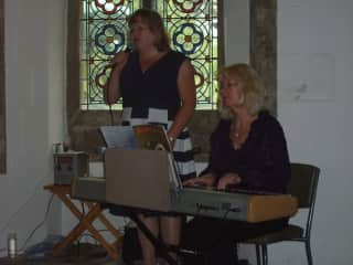 Emma playing piano with her student in church